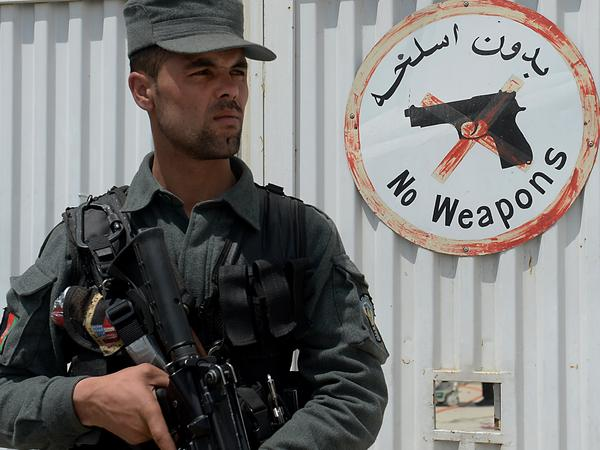 An Afghan police officer kept watch Thursday at the gate of the Cure hospital in Kabul. Earlier, authorities say, a security guard at the hospital opened fire — killing three American citizens.