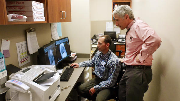 Dr. Billy Oley (left) talks with Dr. William George in the Beartooth Billings Clinic in Red Lodge, Mont. The hospital became part of the Billings Clinic system in exchange for help with its digital medical records.