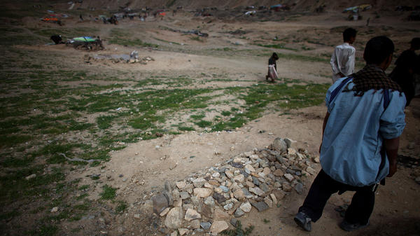 A man walks past a fresh grave in the Kamar Kulagh slum outside of Herat.