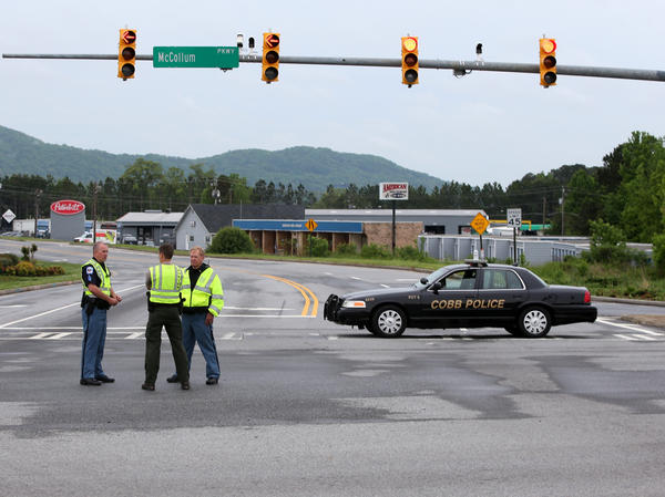 Cobb County Police block off Old US 41 Highway after an early morning workplace shooting at the Airport Road FedEx facility on Tuesday in Kennesaw, Ga.