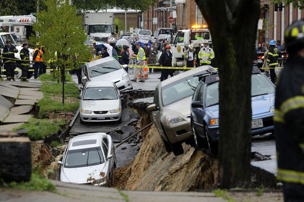 Cars teetered precariously in Baltimore after heavy rain caused a retaining wall to fail. Other vehicles were sent tumbling onto train tracks below.