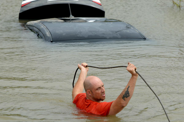 Michael Harrell of J&J Towing attaches a tow cable to a car that was swept off the road by torrential rains in Pensacola, Fla.