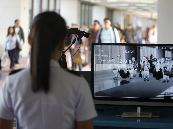 Airline passengers traveling from the United Arab Emirates pass through a scanner designed to detect people with a fever in Manila, the Philippines, in April.