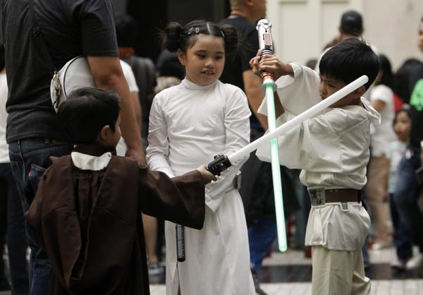 Philippines: Costumed children play with their light sabers inside a Manila-area mall for <em>Star Wars</em> Day.