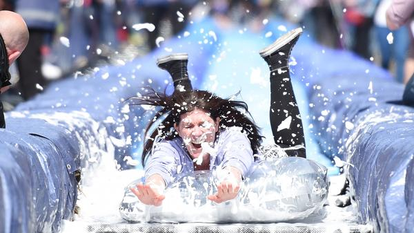 A woman slides on the nearly 300-feet Bristol Park and Slide project, an interactive temporary installation by artist Luke Jerram in the center of Bristol in southwest England Sunday.