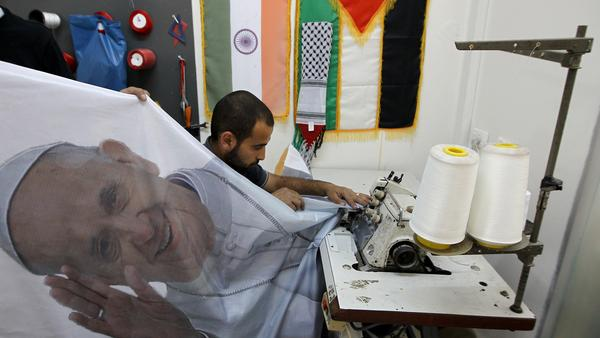 A Palestinian man works on a banner bearing a portrait of Pope Francis at a printing house in the West Bank city of Ramallah in anticipation of this week's papal visit.