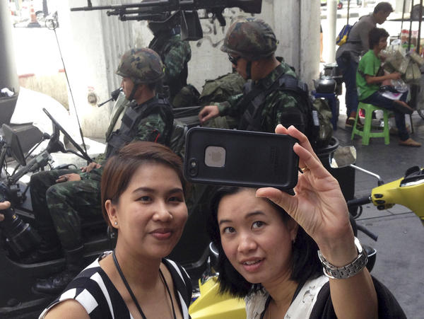 Residents stop to take a photo of themselves at a military checkpoint in central Bangkok on Tuesday. Thailand's army declared martial law in a surprise move it says is aimed at quelling political unrest.
