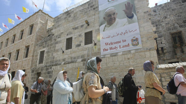 Tourists walk past a poster of Pope Francis hanging on the Church of the Nativity in the West Bank town of Bethlehem on Monday. Pope Francis' trip to the Mideast later this week will commemorate the 50th anniversary of a historic rapprochement between Catholics and Orthodox, who split nearly 1,000 years ago.