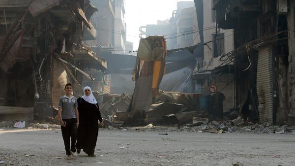 Syrians walk through a destroyed neighborhood in the city of Homs, on May 12. President Obama says he will be increasing aid to moderate Syrian rebels who have been battling President Bashar Assad's forces.