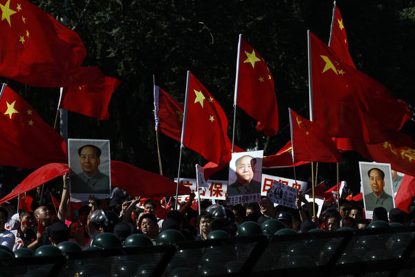 Anti-Japan protesters hold portraits of the late Communist leader Mao Zedong and Chinese national flags while marching on a street outside the Japanese embassy in Beijing on Sept. 18, 2012.