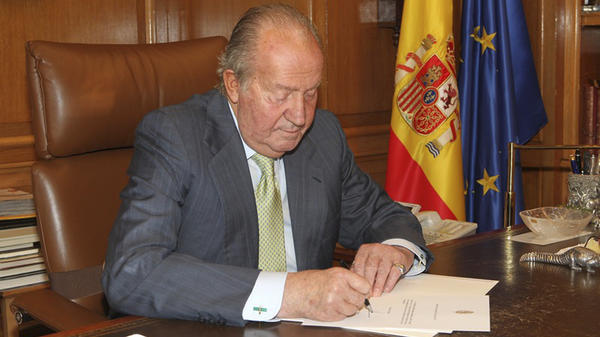 Spain's King Juan Carlos signs a document in the Zarzuela Palace, planning his abdication, in this photo released by the Royal Palace. Juan Carlos will be replaced by his son, Crown Prince Felipe.