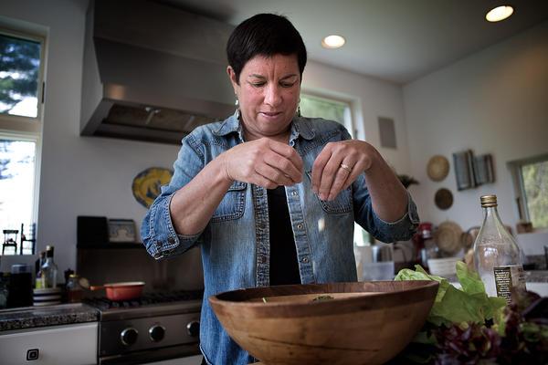 Kathy crumbles feta cheese into the salad. (Jesse Costa/WBUR)