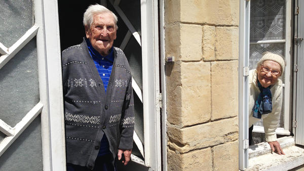 "Lucien (left) and Germaine Rigault lean out of their home in La Cambe, a tiny village in Normandy a short distance from Omaha Beach. The couple, in their 80s, were in La Cambe during the Allied landing on June 6, 1944, and live there still. ""We were scared,"" Lucien says of that day, ""but very happy to be liberated."""