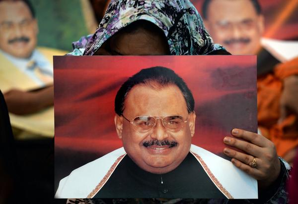 Supporters of Pakistani politician Altaf Hussain hold photographs of him, at a sit-in in Karachi. The city, home to more than 20 million, has largely ground to a halt since his arrest this week in London. Hussain is the leader of the Muttahida Quami Movement, or MQM.