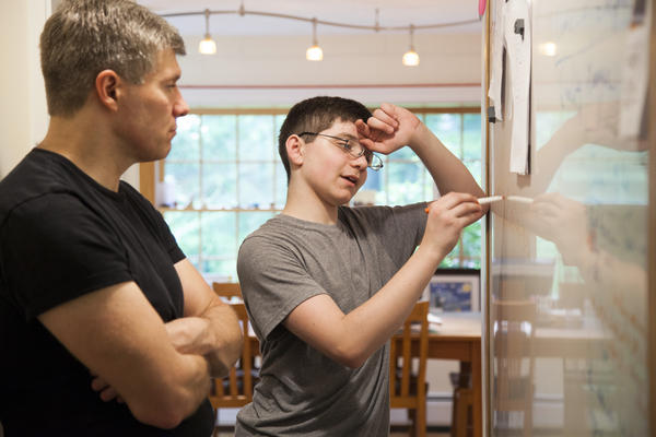 Ed and David work through problems for an algebra final. Both father and son hope the bionic pancreas will be approved for use by the time David goes to college.