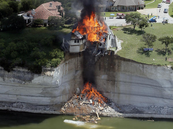 A house is deliberately set on fire Friday, days after part of the ground it was resting on collapsed into Lake Whitney, Texas.