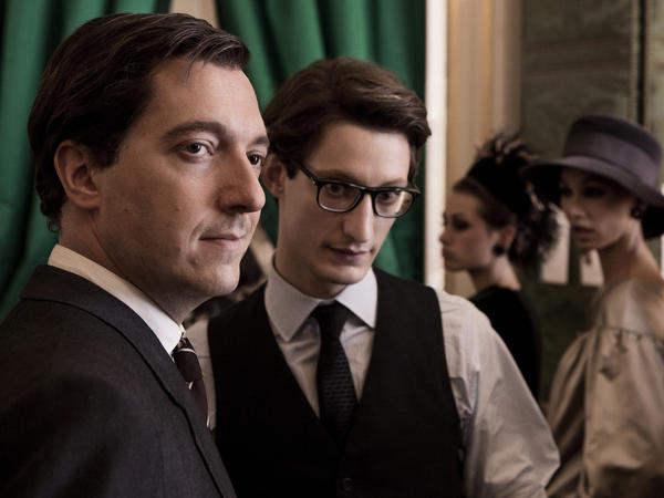 The film depicts the relationship between Pierre Berge (Guillaume Gallienne, left) and Yves Saint Laurent (Pierre Niney) as both interactive and supportive.