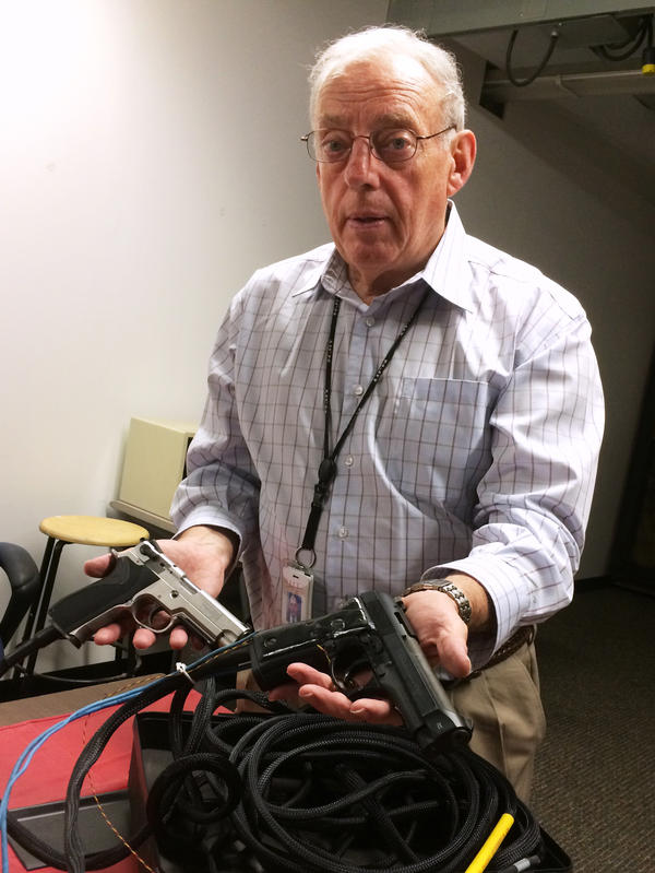 William Marshall of the New Jersey Institute of Technology with two specially modified guns used for research on grip sensor technology.