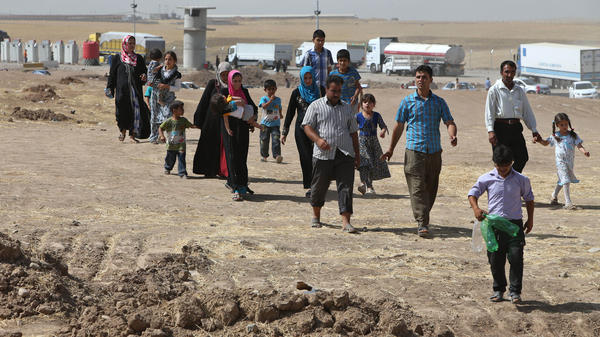 Iraqis who have fled as the Sunni extremist group ISIS has spread in northern Iraq enter a camp for displaced people between the Iraqi city of Mosul and the Kurdish city of Irbil on Thursday. Iraq's leader says he welcomes Syria's attacks on ISIS.