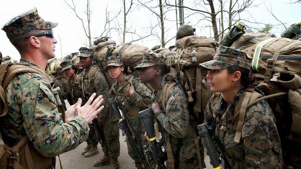 Sgt. Jarrod Simmons speaks to his squad of Marines before they head out on a training march with 55-pound packs on Feb. 22, 2013, at Camp Lejeune, N.C. The Marines and the other military branches must open combat jobs to women in 2016. More than 160 female Marines are taking part in a grueling training program that begins this summer.