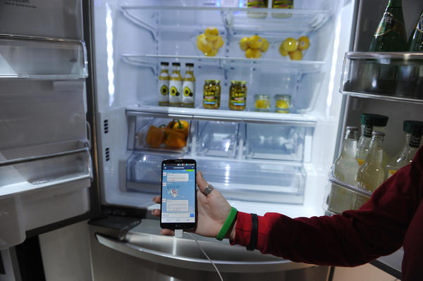 A LG representative shows a smartphone with Home Chat in front of a LG smart refrigerator during the 2014 International CES, January 10 in Las Vegas, Nevada. The LG Smart Home system with the Home Chat smart platform allows users to communicate with home appliances via text message. (Robyn Beck/AFP/Getty Images)