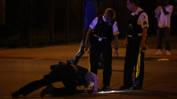 Police investigate the scene of a shooting at 75th Street and Stewart Avenue on Saturday in Chicago. At least 50 people were shot in the city, nine of them fatally, in a wave of violence over the Fourth of July weekend.