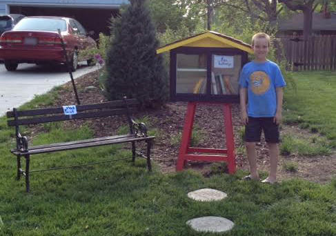 Spencer Collins, 9, with his Little Free Library that a neighbor complained  was an eyesore and violated the town's zoning ordinances. (Sarah Collins)