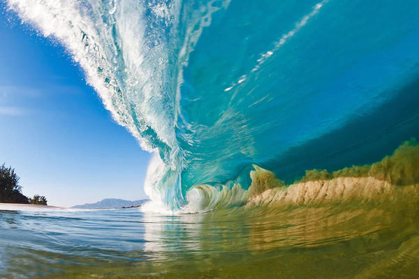 """A large wave on the North Shore of Oahu, Hawaii, sucks sand off of the seafloor and into the wave itself. This photo is the cover image of Clark Little's <a href=""""http://www.clarklittlephotography.com/book.php"""">latest coffee table book</a>, <em>Shorebreak</em>."""