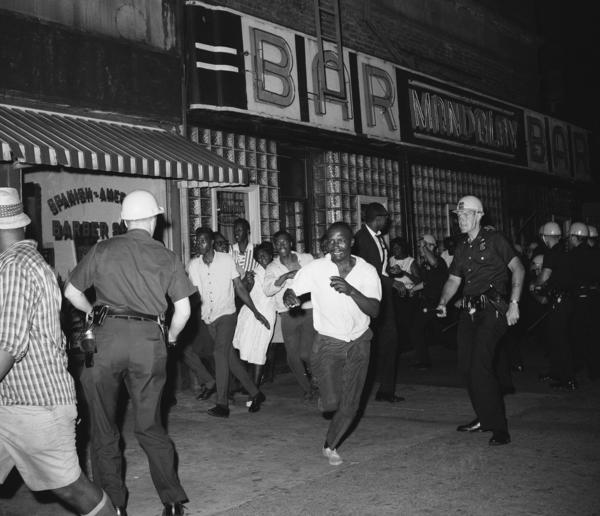 Members of New York's Harlem community run from steel-helmeted police swinging nightsticks in an effort to break up a street gathering on July 19, 1964.