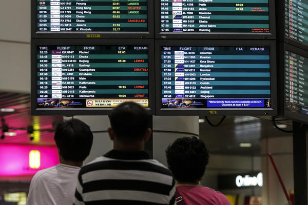 "Passengers at Kuala Lumpur International Airport look at a flight information board. ""Our thoughts and prayers are with those on board the Malaysia Airlines airplane lost over Ukrainian airspace, as well as their families and loved ones,"" Boeing said in a statement. ""Boeing stands ready to provide whatever assistance is requested by authorities."""
