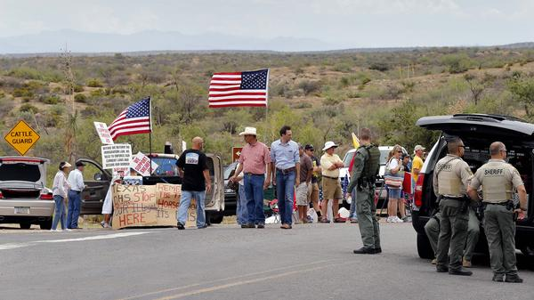 In Oracle, Ariz., on Tuesday, protesters gather near the entrance to a juvenile facility in an effort to stop the arrival of a busload of Central American immigrant children. The bus never arrived.