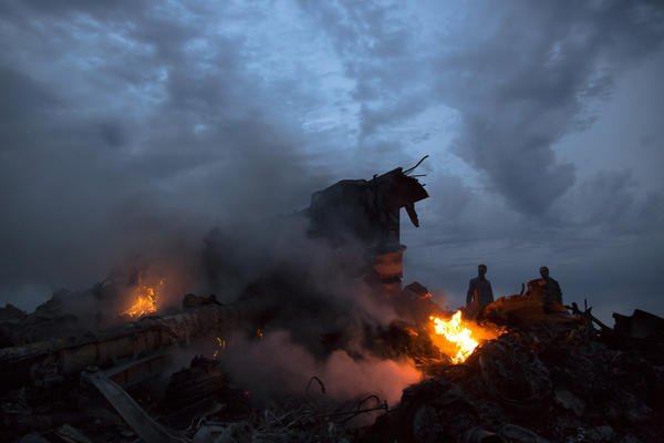 People walk amongst the debris at the crash site of Malaysia Airlines Flight MH17, which went down in eastern Ukraine on Thursday.