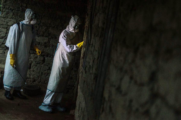 The burial team waits outside the house of someone who may have died of Ebola.