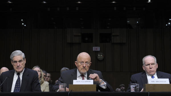 """Director of National Intelligence James Clapper (center), accompanied by FBI Director Robert Mueller (left) and CIA Director John Brennan, testifies on Capitol Hill on March 12, 2013. When questioned, Clapper said the NSA did not collect data on Americans. He later acknowledged his response was """"clearly erroneous."""""""
