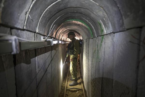 An Israeli army officer gives journalists a tour on July 25 of a tunnel allegedly used by Palestinian militants for cross-border attacks, at the Israel-Gaza border.