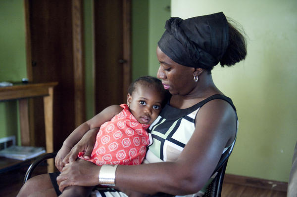 Decontee Sawyer, wife of Liberian government official Patrick Sawyer, a U.S. citizen who died from Ebola after traveling from Liberia to Nigeria, cradles her 1-year-old daughter Bella at her home in Coon Rapids, Minn., Tuesday, July 29 (Craig Lassig/AP).