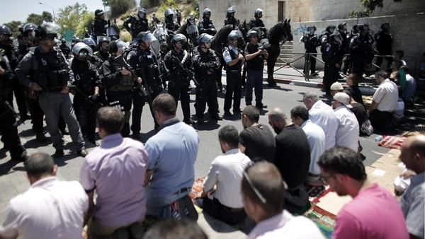 Members of the Israeli security forces stand guard as Palestinian Muslims perform Friday prayers on a street outside the Old City of Jerusalem on Friday.