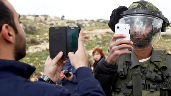 A Palestinian man and a member of the Israeli security forces take pictures of each other with their mobile phones near Ramallah, in the West Bank, on March 14. Israelis and Palestinians used to have regular contact, but today they are increasingly segregated.