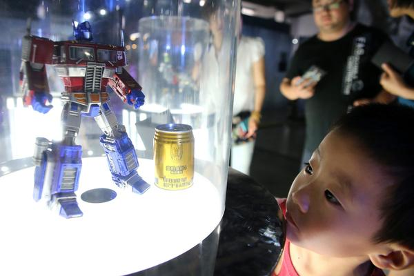 A boy looks at a toy model of Transformers character Optimus Prime on display at a Transformers Model Show in Qingdao city in northeast China.