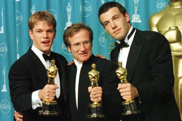 Actor-writers Matt Damon (left) and Ben Affleck pose with Williams holding the Oscars they won for <em>Good Will Hunting</em> at the 70th Annual Academy Awards in 1998.