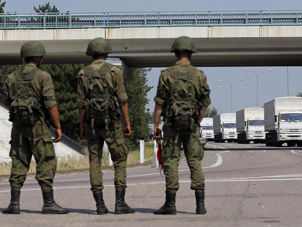 A Russian convoy of trucks carrying humanitarian aid for Ukraine drives along a road as Russian servicemen look on, near Kamensk-Shakhtinsky, Rostov region, on Thursday.