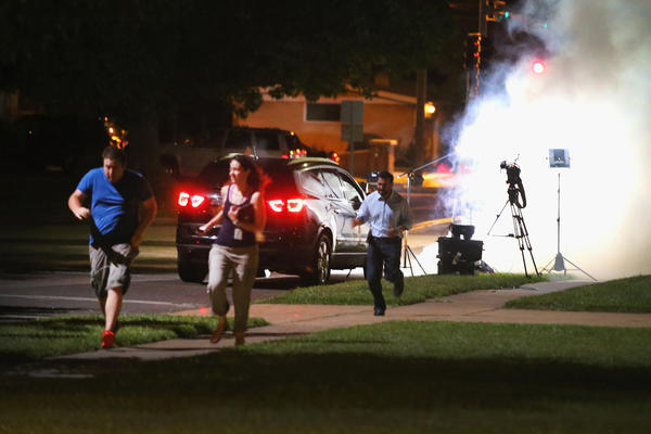 An Al Jazeera television crew, covering demonstrators protesting the shooting death of teenager Michael Brown, scramble for cover as police fire tear gas into their reporting position.