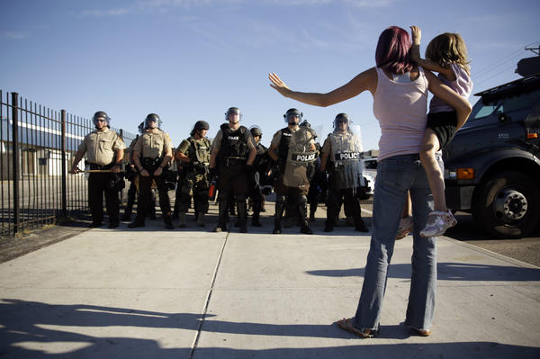Protester Janelle Pittman holds her 6-year-old daughter, Kat, as police in riot gear stand guard.