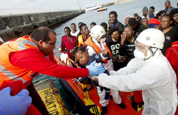 An African migrant infant is handed off by a member of the Red Cross to a member of the Spanish coast guard in the port of Tarifa on Tuesday.