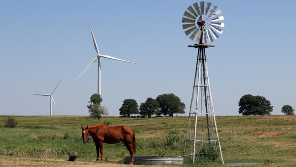 A wind-powered water pump and a wind-driven electricity turbine share a field near the town of Calumet in western Oklahoma.