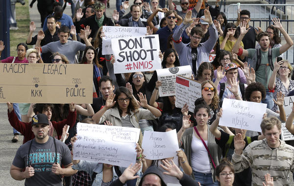 """A crowd raises their arms while chanting """"Hands Up, Don't Shoot"""" during a protest for Michael Brown of Ferguson, Mo., in San Francisco."""