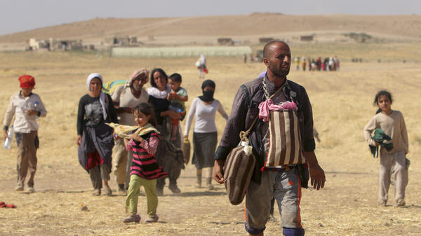 Displaced people from the minority Yazidi sect in northern Iraq walk toward the Syrian border last week.