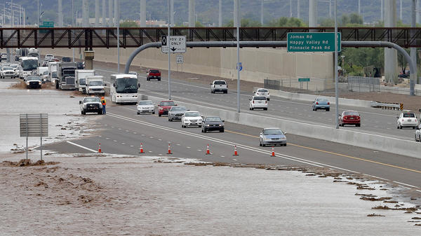 Flash<strong>-</strong>flood waters from the overrun Skunk Creek flood I-10 in northwestern Phoenix. Flooding from heavy rain forced authorities to close several major roads, including a portion of Interstate 17.