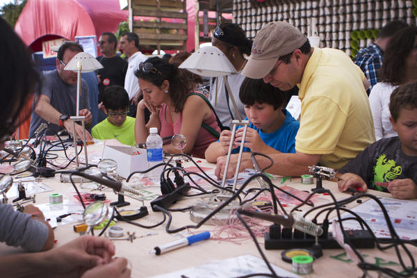 Kids of all ages learn to solder tiny circuit boards with LEDs.