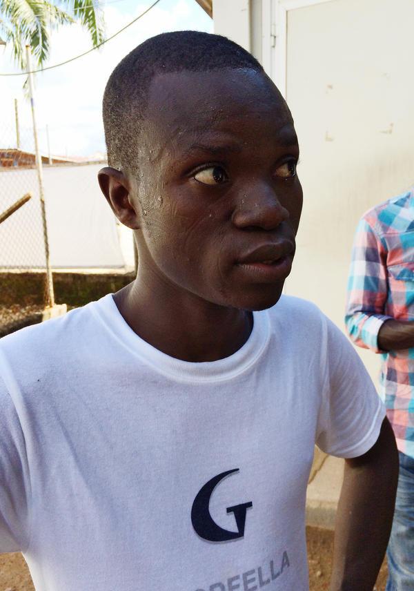 Survivor Dauda Fullah now works in the Ebola ward in Kenema, Sierra Leone. Here he emerges soaking wet from his shift inside the stifling ward, where he wears full body protection.